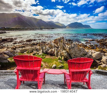 Two armchairs chaise longue by Atlantic ocean. Boulders Penguin Colony in the Table Mountain National Park, South Africa. African penguins among stones. The concept of ecotourism