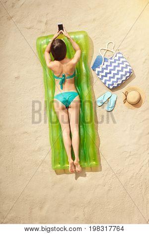 Young female traveler tourist top view sunbathing using smartphone
