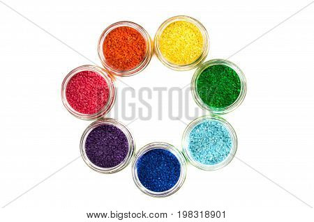 colored rice in glass jars is by colors of the rainbow. isolate