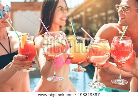 Group of friends in the swimming pool drink