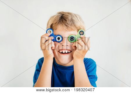 A boy in a red T-shirt looks through a spinner and smiles