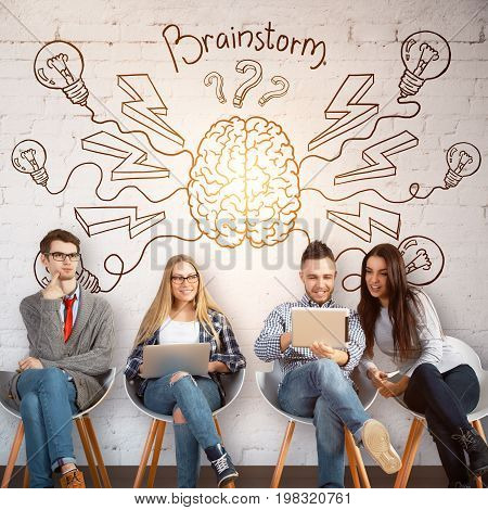 Cheerful young businesspeople sitting on chairs and using laptops ni brick interior with glowing brain sketch on wall. Brainstorm and teamwork concept