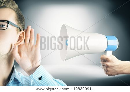 Handsome young man listening to loud speaker announcement held by hand on gray gradient background. Communication concept