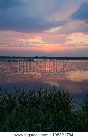 The sunset reflects on the waters of a small lake in rural Saskatchewan.