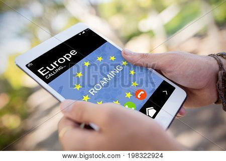 Roaming text and European Union flag on mobile display against close-up of man hands using digital tablet