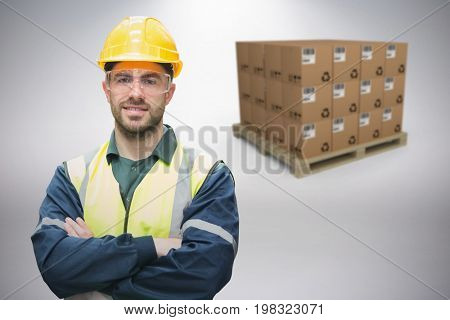 Manual worker wearing hardhat and eyewear against grey background