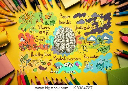 Top view of orange desktop with healthy brainstorm sketch and supplies. Food for brain concept