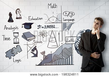 Thoughtful young man standing on white brick wall background with brain sketch. Left hemisphere concept