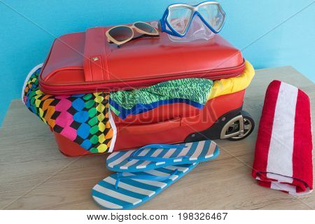 Suitcase with things for spending summer vacation things prepared for travel. red suitcase with clothing on table