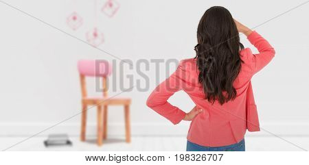 Elegant brunette standing back to camera and looking away against decoration over empty wooden chair and books against wall