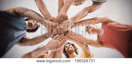Directly below shot of friends standing with stacked hands against sky