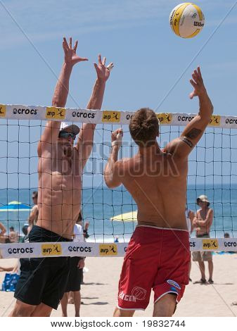 MANHATTAN BEACH, CA. - JULY 18: Mike Placek spikes the ball and Austin Rester attempts to block him at the AVP Manhattan Beach Open on July 18, 2009 in Manhattan Beach, CA.