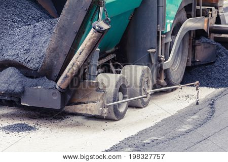 Paver makes the new asphalt on the road. Roadwork with heavy machinery.