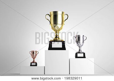 Golden silver and bronze winner's cups placed on white pedestals. Light background. Award concept. Mock up 3D Rendering