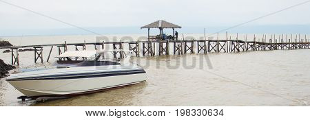 The Speedboat docked with long wooden bridge.
