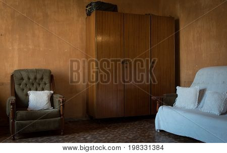 Interior of an old house living room with old sofas and cupboard for storage