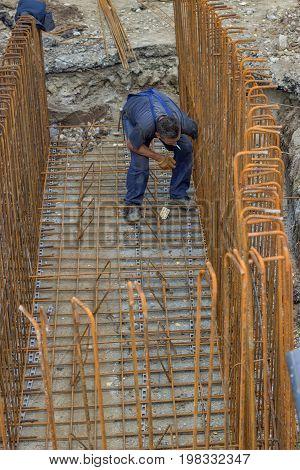 Worker Preparing Reinforcing Rod Framework For Concrete Pouring