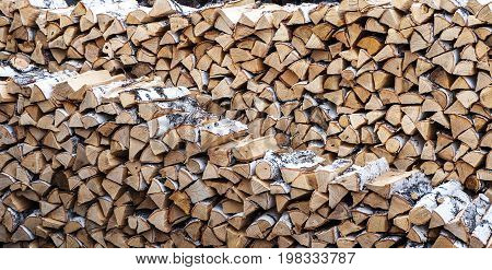pile of chopped firewood Birch. Harvesting of firewood.
