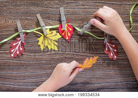 Autumn Background With Colorful Different Leaves Of Paper And Wooden Clothespins On A Wooden Backgro