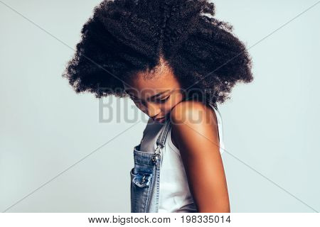 Shy Young African Girl Standing Sideways Against A Gray Backgrou