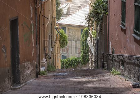Narrow street between old unkempt buildings near the Spianata di Castelletto in Genoa city Italy.