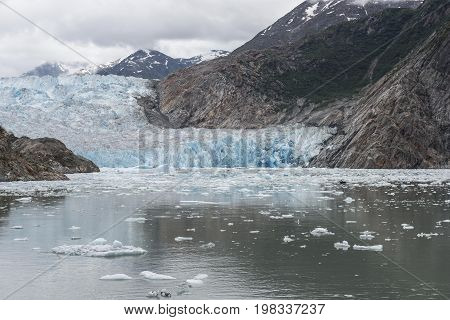 Blue and white glacier with ice bergs in the ocean