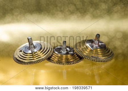 Watch Repair: Vintage Pocket Watch Fusee Cones Resting on a Golden Surface