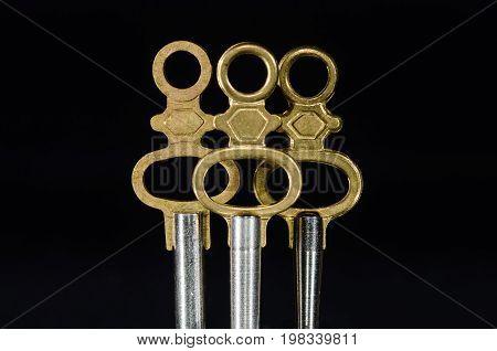 Three Antique Brass Pocket Watch Keys Standing in the Darkness