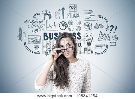 Young woman with dark long hair is wearing a white sweater and holding her glasses with a thick frame. She is looking to the distance while standing near a gray wall with a business idea sketch