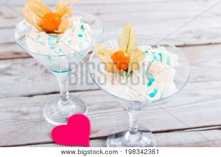 Two desserts pav meringue with cardboard hearts.