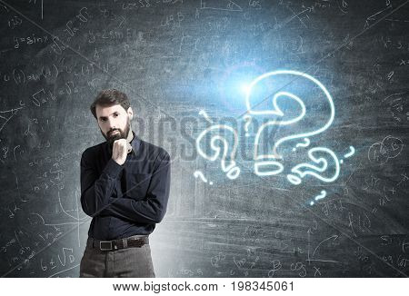 Portrait of a pensive bearded businessman wearing a black shirt and standing near a blackboard with blue question marks. Toned image
