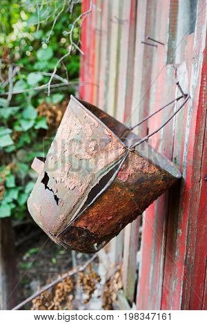 Firefighter Shield With An Old, Rusty, Leaky Bucket. Abandoned Garden Plot. Rural Landscape.