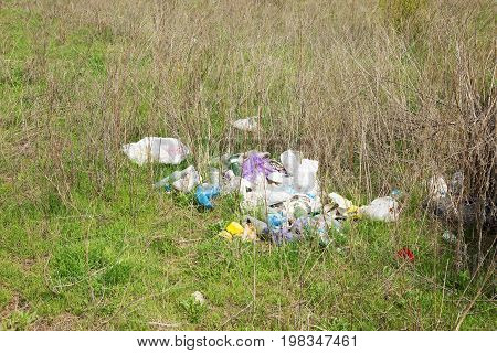 Piles Of Garbage And Glass Bottles Lying On The Ground. Garbage Dump. Pollution Of The Environment.