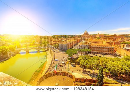 aerial view at sunset of Vittorio Emanuele II Bridge and Tevere river from overlook of Castel Sant'Angelo castle in Rome city, Italy. Saint Peter basilica on background and italian flag waving.