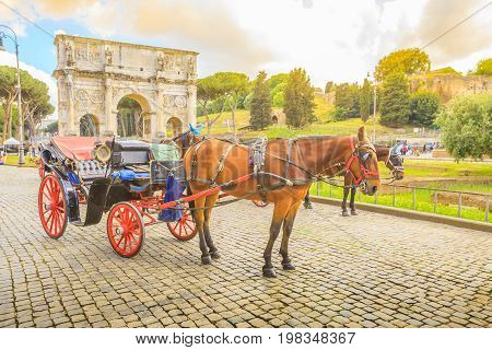 Rome, Italy - May 12, 2016: Typical horse-drawn carriage with tourists in front of Colosseo, Colosseum, with Arco di Costantino, one of the symbols of Italy.