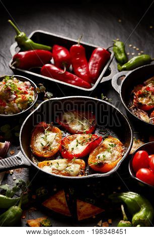 Grilled sweet peppers poppers stuffed with cheese and herbs, mix  delicious appetizers on a black background