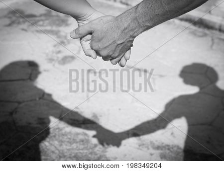 Hands of two lovers intertwined with a silhouette