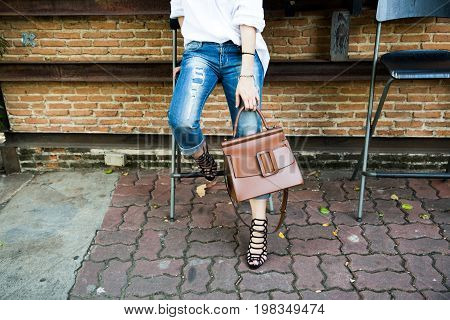 Handbag in hand and jean of stylish woman fashionable girl , Female Fashion Concept