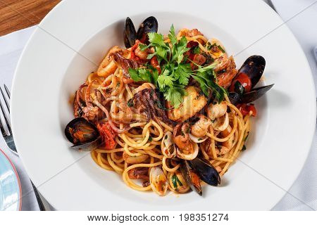 spaghetti sea food on white plate on white plate with full serving