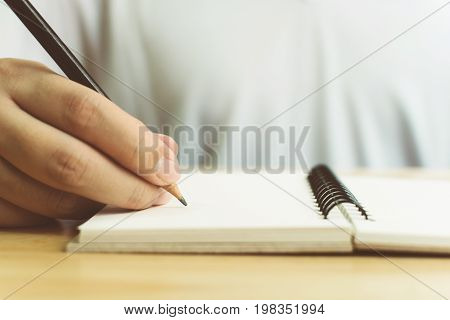 Hand of man with pencil writing on notebook