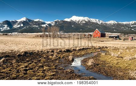 A ranch farm homestead looks cold and bright during winter frost