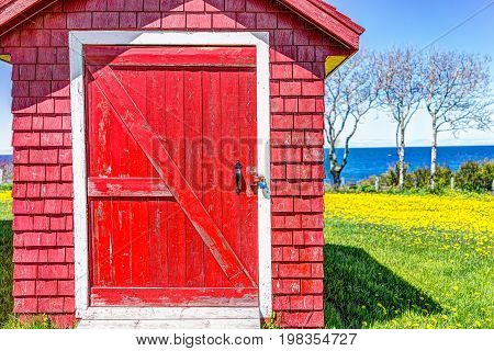 Red painted wooden shed door with yellow dandelion flowers and view of Saint Lawrence river in La Martre in the Gaspe Peninsula Quebec Canada Gaspesie region