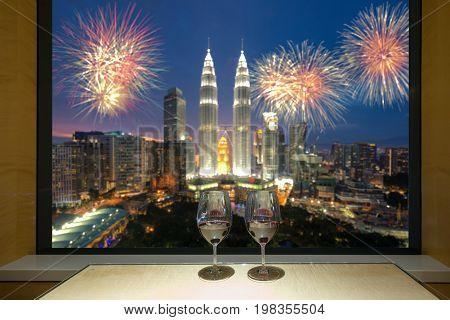 Closeup of a glasses of red wine at windowsill against night Kuala lumpur city view of urban city sky line blurring lights. Malaysia.