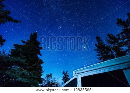 Night Sky Full Of Stars Above An Rv Tent Trailer And Tall Pine Trees In The Wilderness