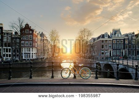 Bicycles on a bridge over the canals of Amsterdam Netherlands. Bicycle is major form of transportation in Amsterdam Netherlands.