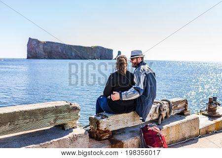 Perce Canada - June 6 2017: Back of couple cuddling on pier dock looking at Rocher Perce rock waiting for boat trip to Bonaventure island in Gaspe Peninsula Quebec Gaspesie region