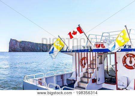 Perce Canada - June 6 2017: Boat for tourist trip to Rocher Perce rock and Bonaventure island in Gaspe Peninsula Quebec Gaspesie region with flags