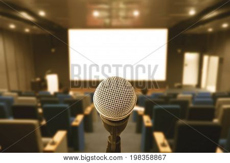 Microphone over abstracts blurred images of meeting rooms or seminar rooms with background as attendees. Vintage style