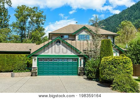 Big family house with wide concrete driveway double wide garage door decorated front yard. Residential house with mountain and blue sky background