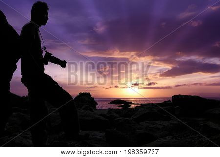 Silhouette photographer standing on the rocks by the sea with purple sky sunrise in the morning.
